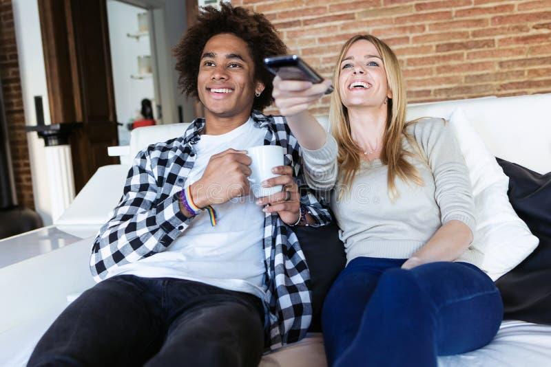 Ändrande kanaler för avkopplade unga par med fjärrkontrollen, medan hålla ögonen på TV på soffan hemma royaltyfria bilder