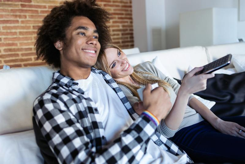 Ändrande kanaler för avkopplade unga par med fjärrkontrollen, medan hålla ögonen på TV på soffan hemma arkivbild