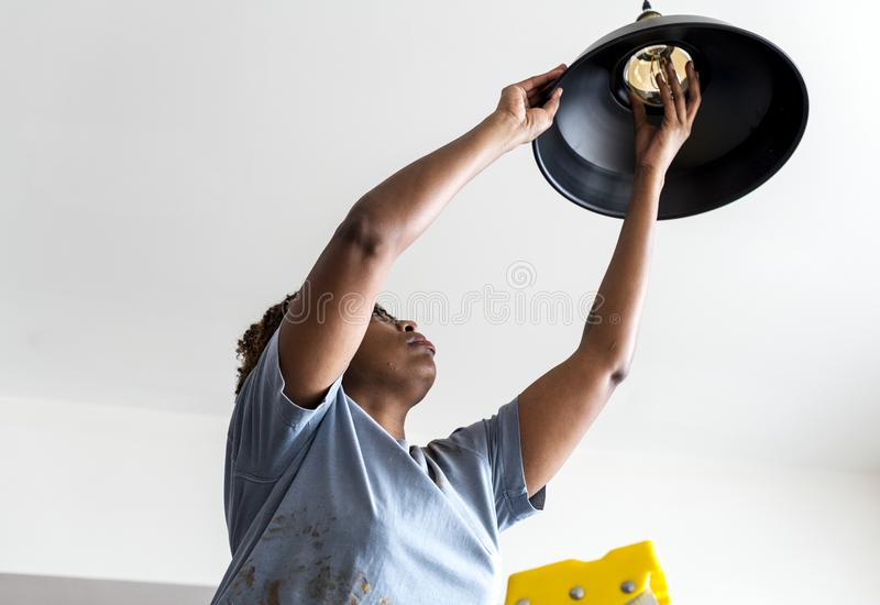 Ändrande lightbulb för kvinna hemma arkivfoto