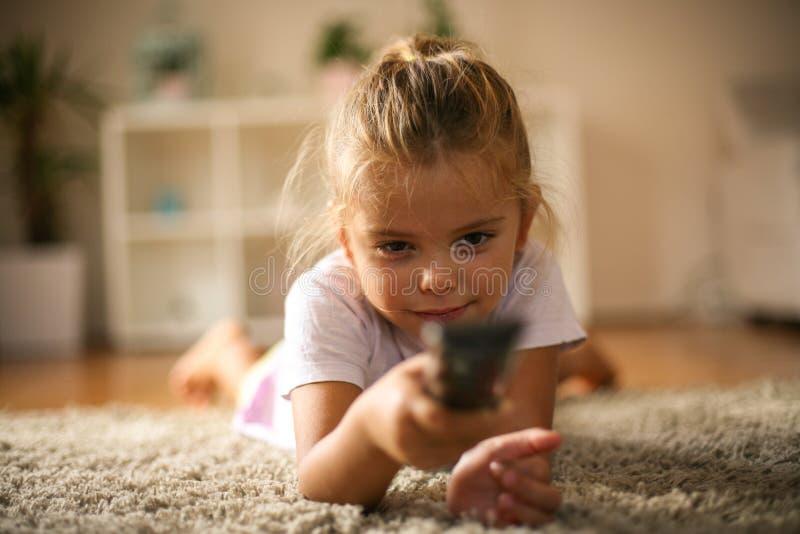 Ändrande TV-kanal för liten flicka med fjärrkontrollen arkivbild