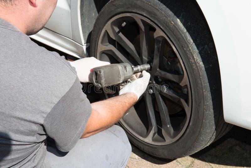 Ändrar den automatiska mekanikern för mannen hjulet av en bil till ett plant gummihjul royaltyfri foto