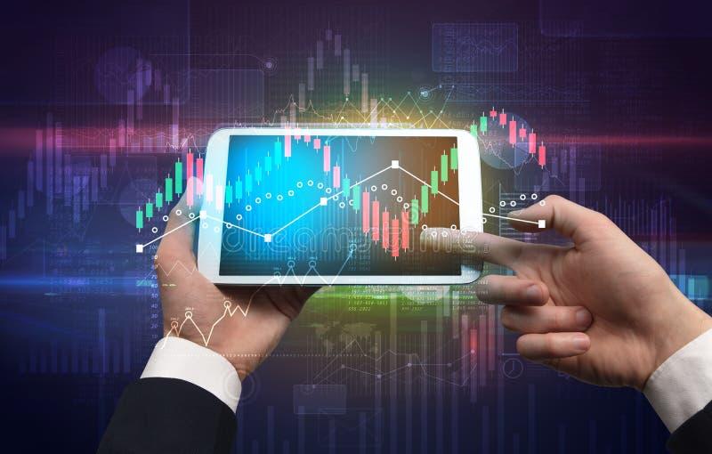Ändrar den hållande minnestavlan för handen med globala rapporter och aktiemarknaden begrepp royaltyfria bilder