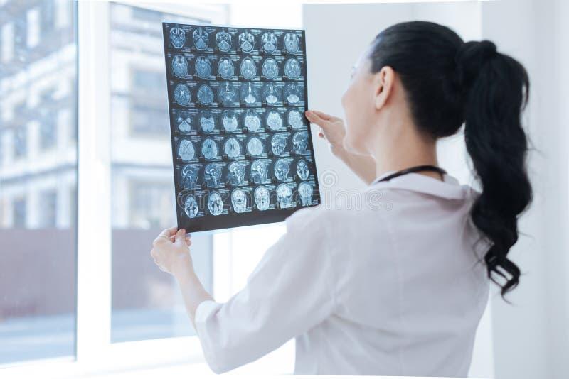 Ändrar den undersökande hjärnan för den förtjusta radiologispecialisten på arbete royaltyfri bild
