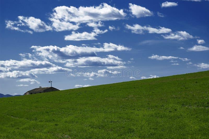 Äng, himmel, moln och tak arkivbild