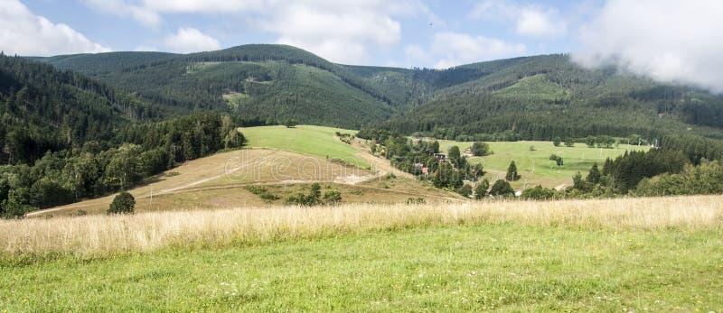 Ängar och fält med Kralicky Sneznik bergskedja med moln över royaltyfria foton