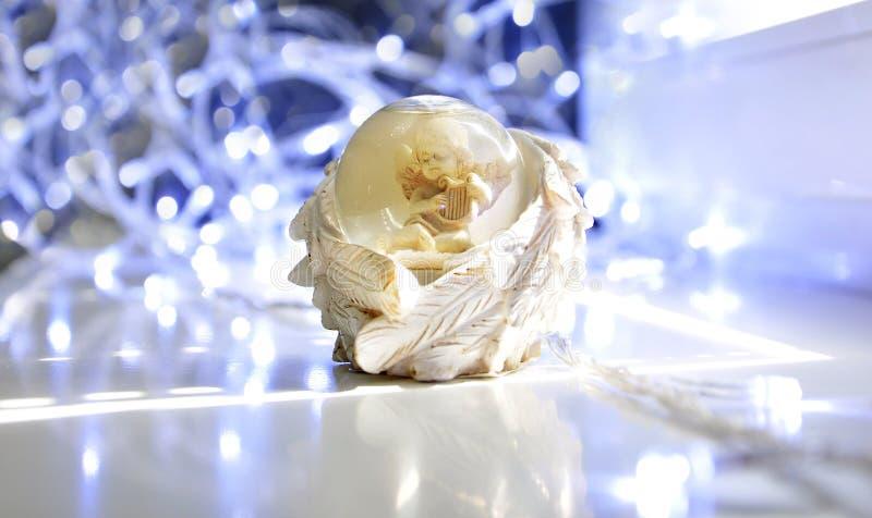 Ängel i en exponeringsglasboll med vingar, dekor för nytt år, bokeh royaltyfri foto