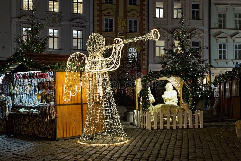 Ängel med hornet som göras av ljusgirlanderna och julkrubba i Prague, Tjeckien arkivbild