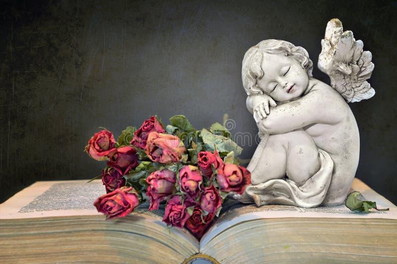 Ängel, rosor och gammal bok på grungebakgrund arkivfoton