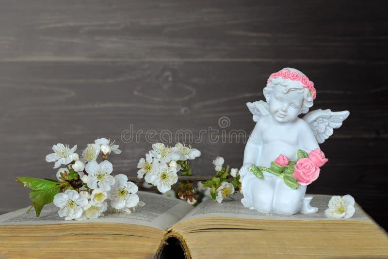 Ängel som knäfaller och rymmer blommor royaltyfri foto