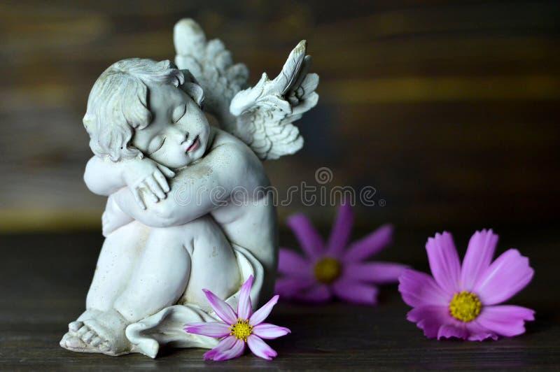 Ängelförmyndare och blommor arkivbild