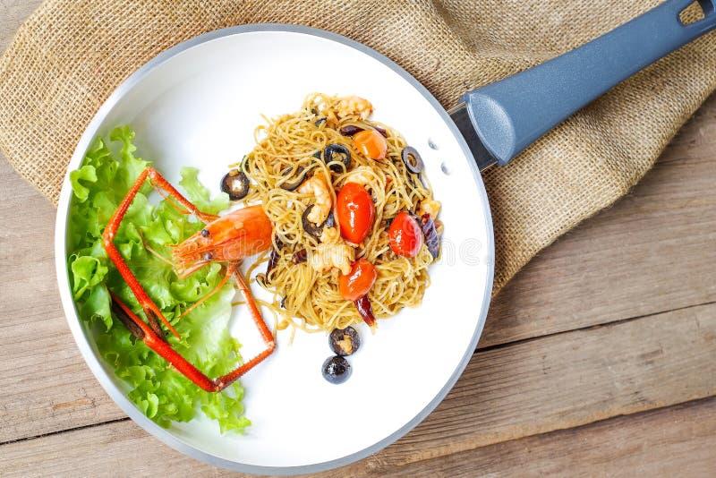 Ängelhårpasta med den jätte- räkan, oliv, tomater och chili royaltyfri bild