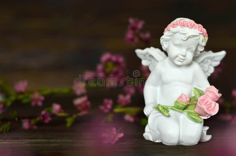 Ängelinnehavgrupp av rosor royaltyfri foto