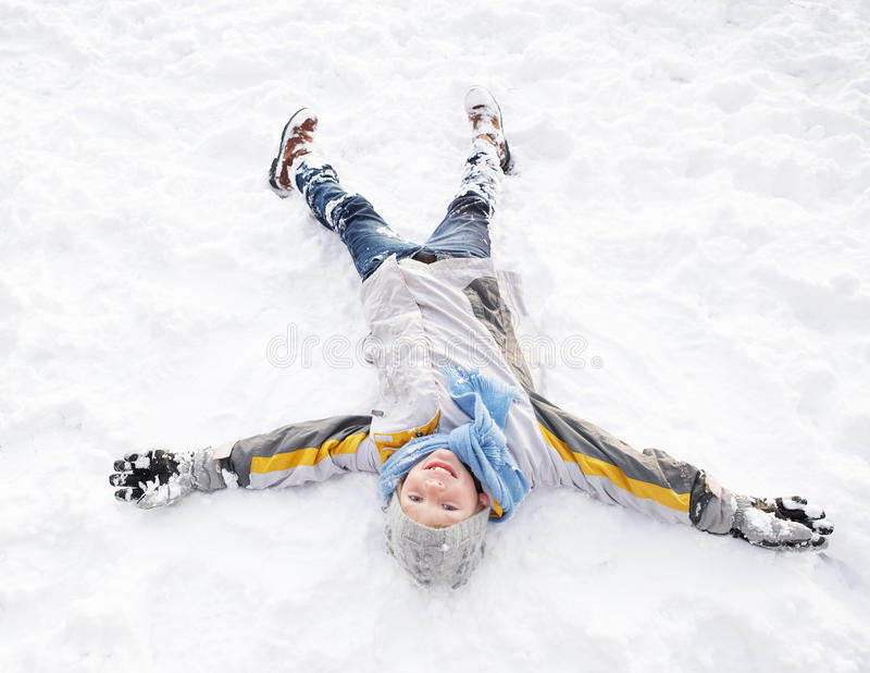 ängelpojkejordning som lägger göra snow arkivfoton