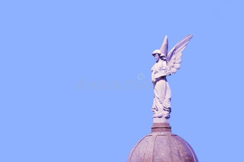 Ängelskulptur i en kyrkogård mot en blå himmel Dödsymbolet och tömmer kopieringsutrymme royaltyfria foton