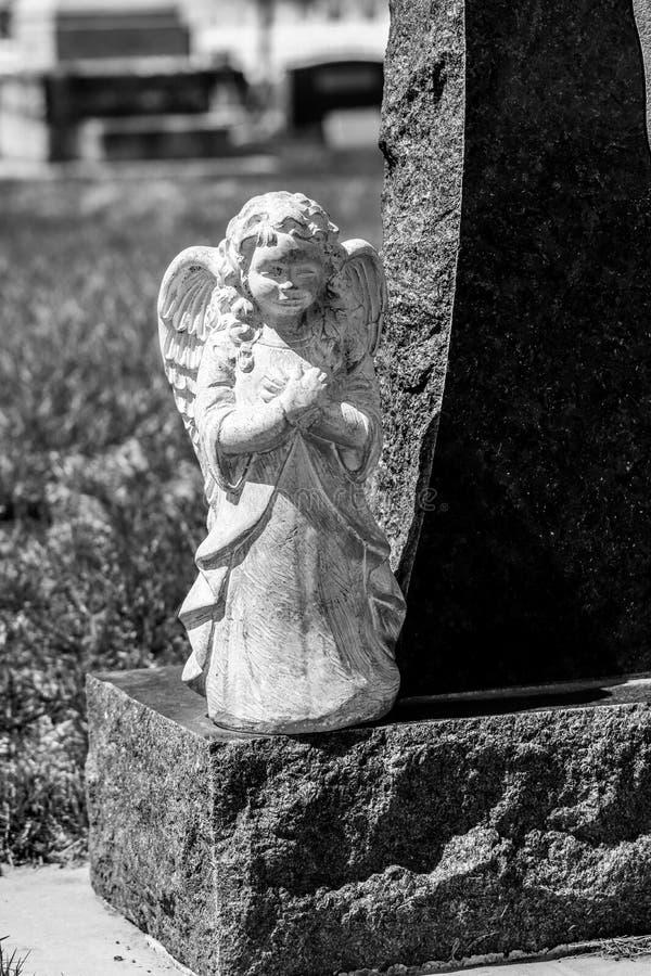 Ängelstaty på sidan av gravstenen arkivfoto