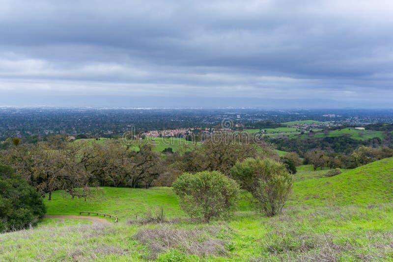 Ängen och kullar på en molnig och regnig dag i det Rancho San Antonio länet parkerar; San Jose och Cupertino i bakgrunden, södra  arkivfoton