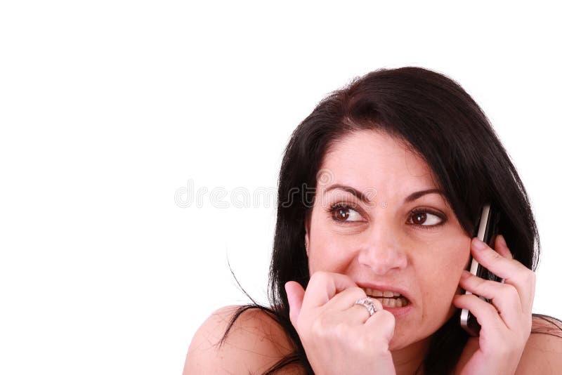 Ängstlich schauende Frau mit einem Telefon stockfoto