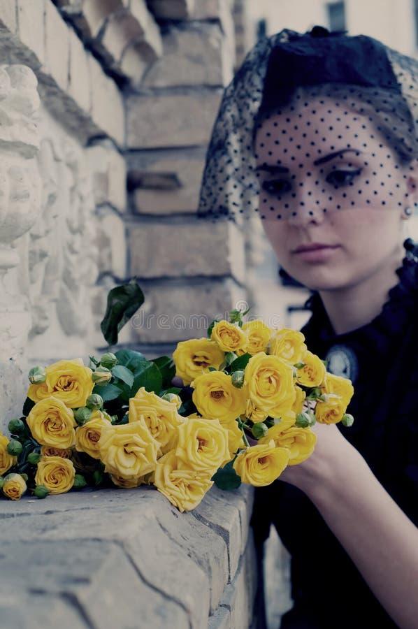Änka som förlägger blommor på gravstenen royaltyfria foton