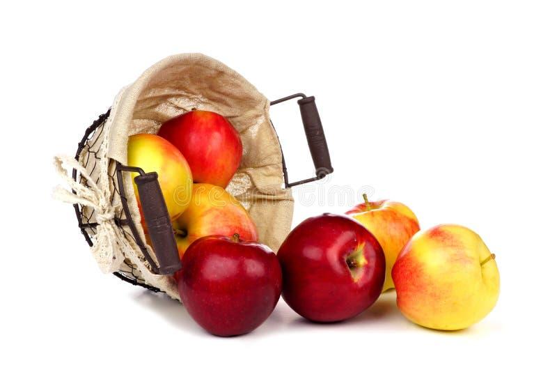 Äpfel, die einen rustikalen Korb lokalisiert auf Weiß überlaufen stockbilder
