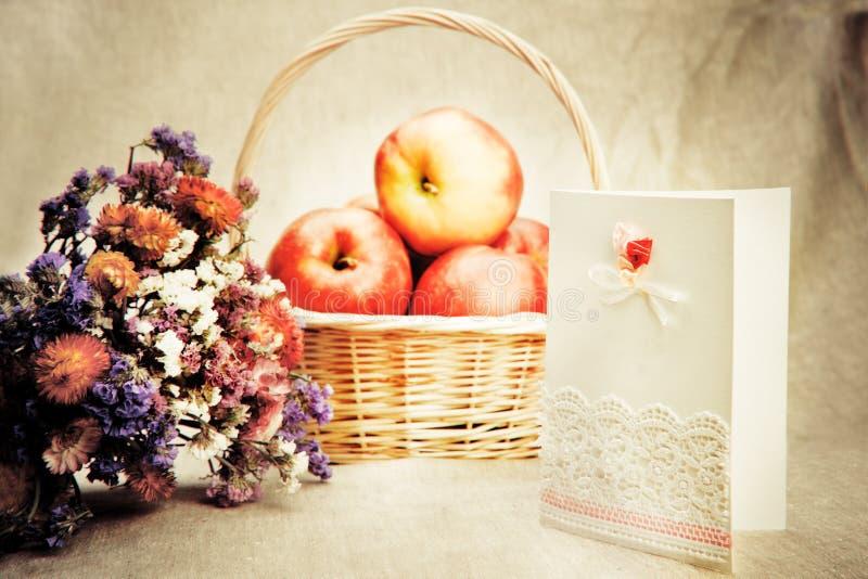 Äpfel im Korb und in den wilden Blumen stockfoto