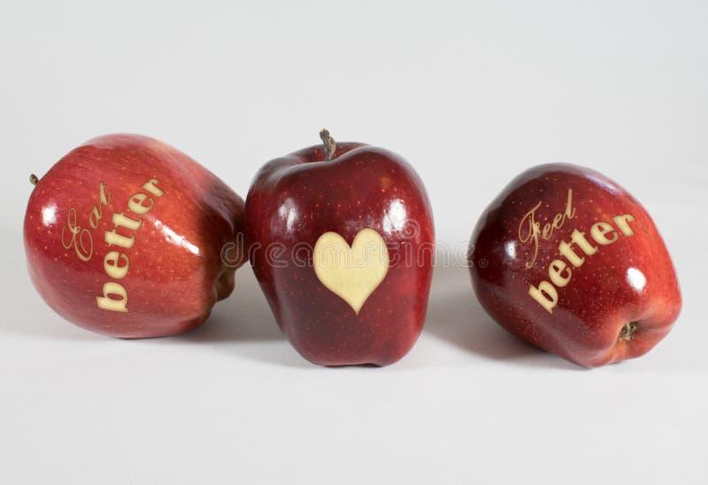 3 Äpfel mit den Wörtern - essen Sie besseres Gefühl besser - und ein Herz stockfotografie