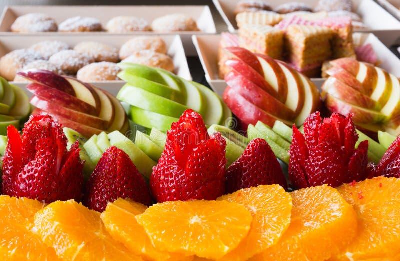 Äpfel mit Erdbeerkiwiorangen und -plätzchen werden für ausgebreitet stockfoto