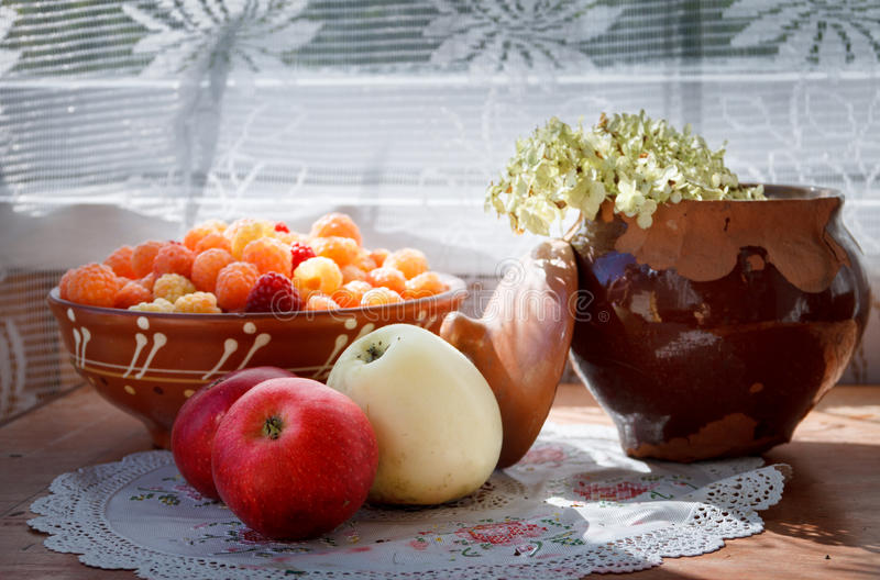 Äpfel, Platte mit Himbeeren und gebrochenes Tongefäß mit Blume im Sonnenlicht lizenzfreies stockfoto