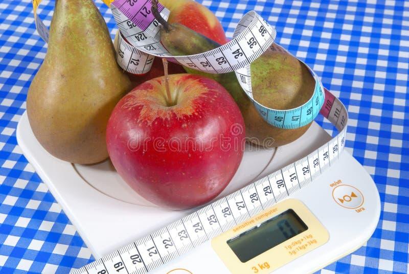 Äpfel und Birnen auf Skala stockbilder