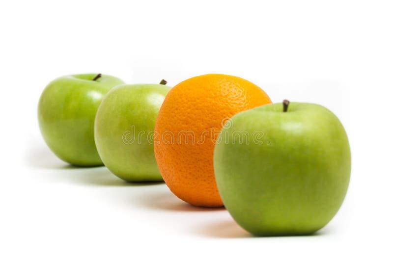 Äpfel und eine Orange stockfotos