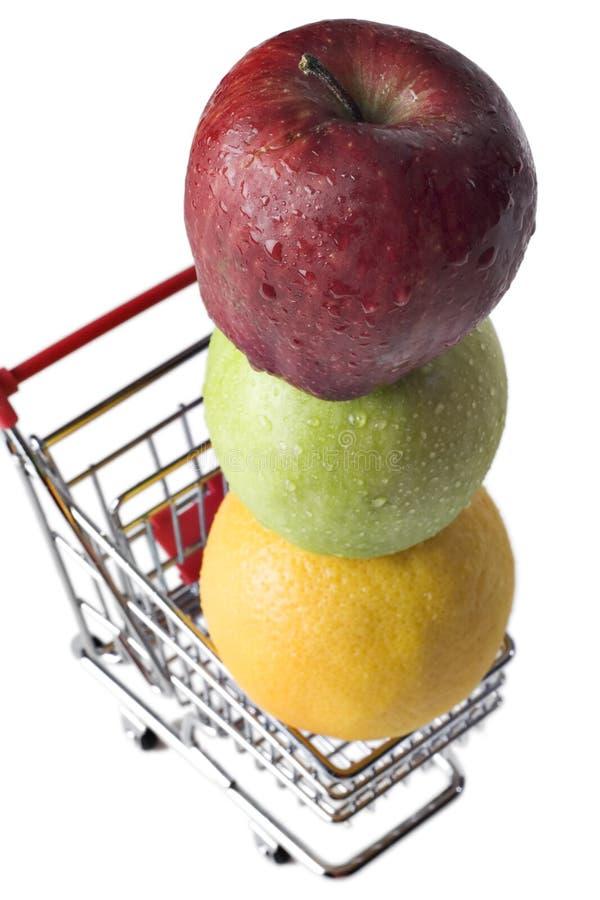 Äpfel und eine Orange in einem MiniEinkaufswagen stockbilder