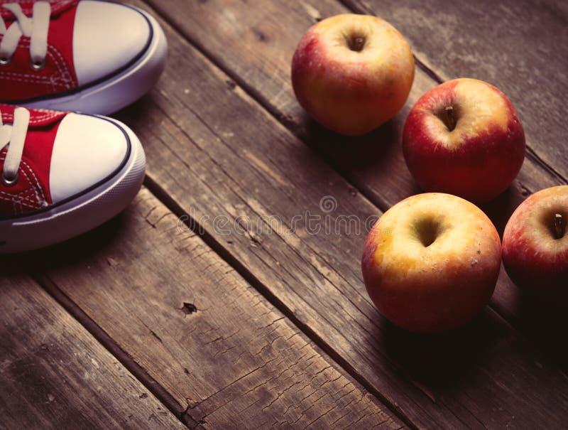 Äpfel und Gummiüberschuhe stockfotos