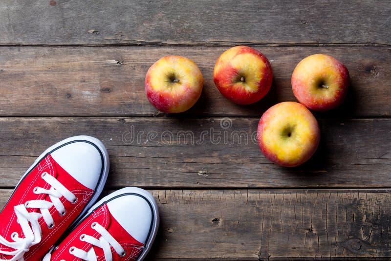 Äpfel und Gummiüberschuhe lizenzfreie stockbilder