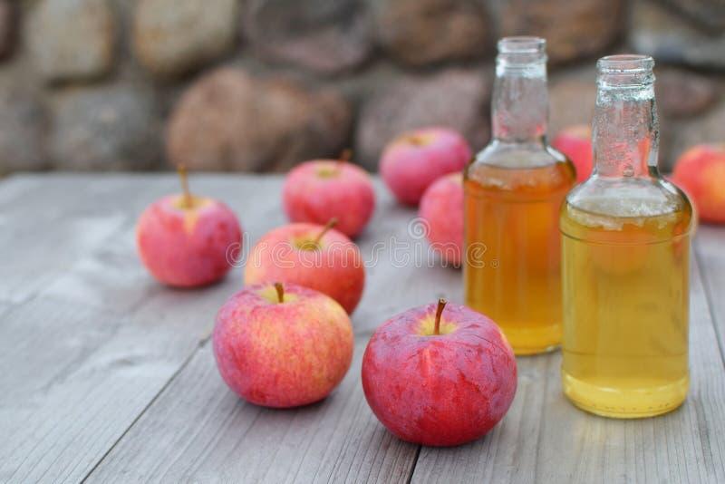 Äppelcider i flaskor och röda äpplen arkivbilder