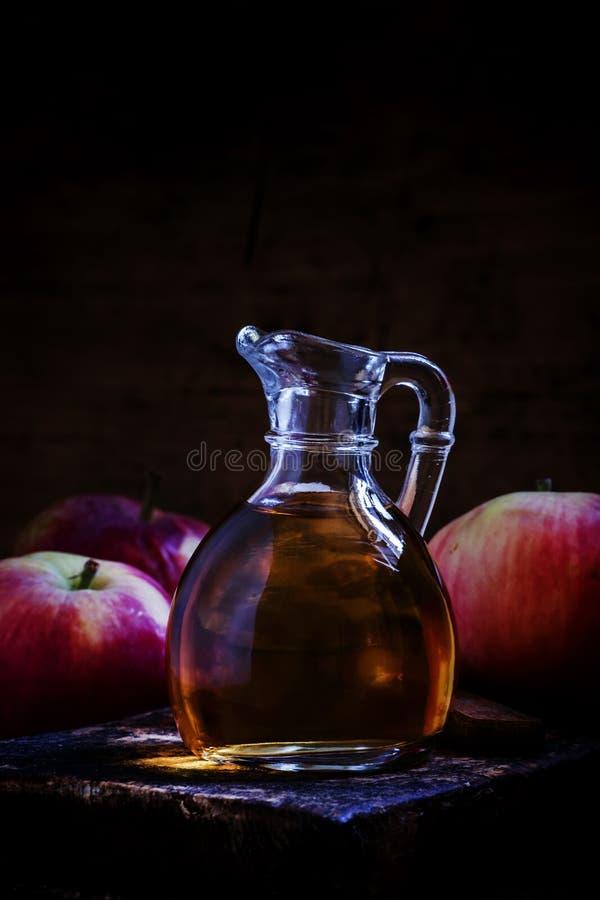 Äppelcidervinäger i en glass tillbringare, nya äpplen, mörka trälodisar arkivfoto