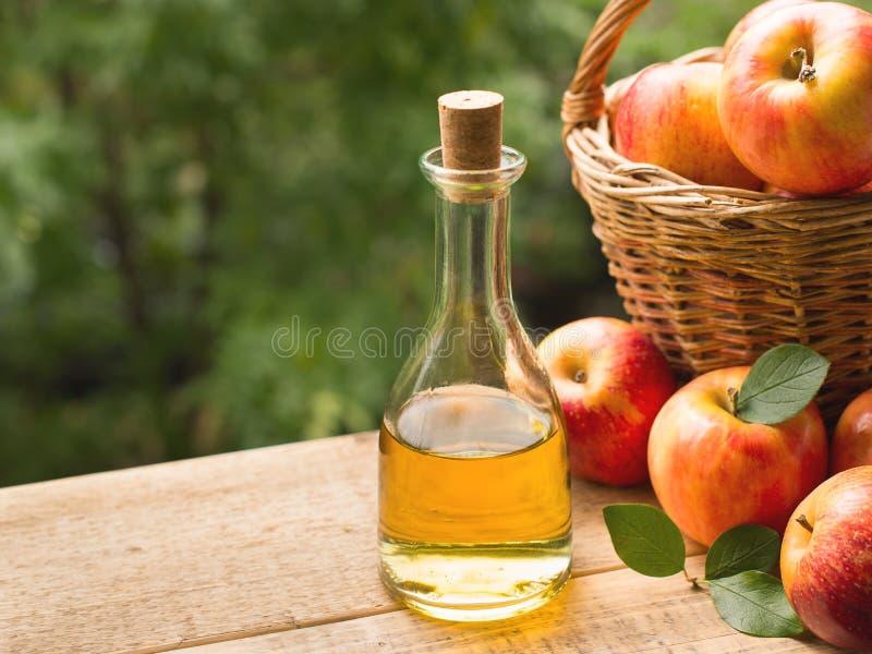 Äppelcidervinäger i flaska med äpplet arkivbild