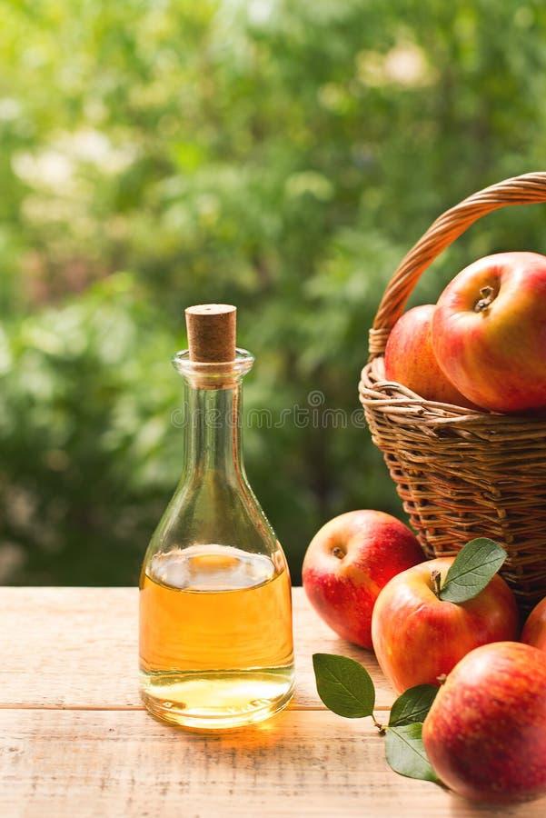 Äppelcidervinäger i flaska med äpplet arkivfoton