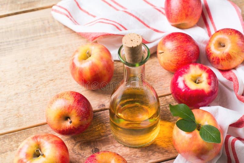 Äppelcidervinäger i flaska med äpplet arkivfoto