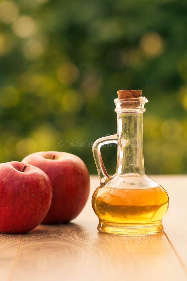 Äppelcidervinäger i glasflaska och nytt rött äpple på woode arkivbild