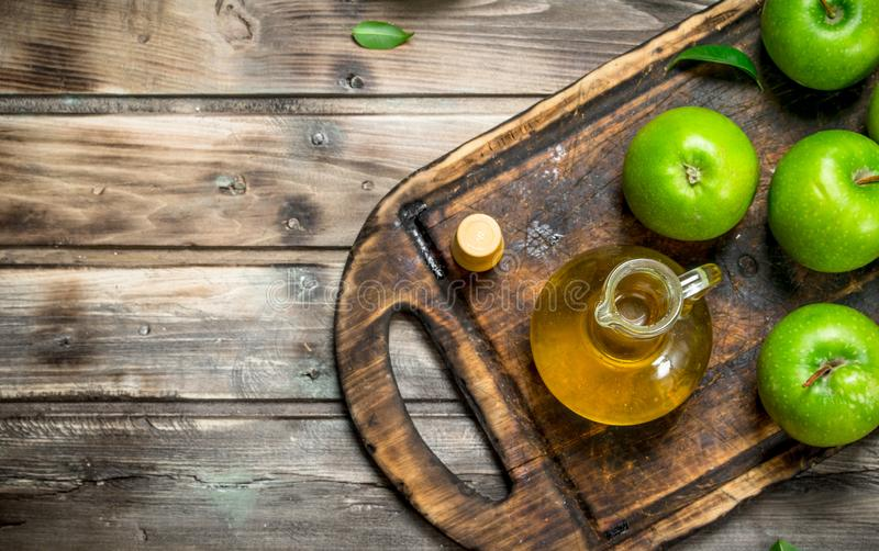 Äppelcidervinäger med gröna äpplen på ett gammalt bräde arkivfoto