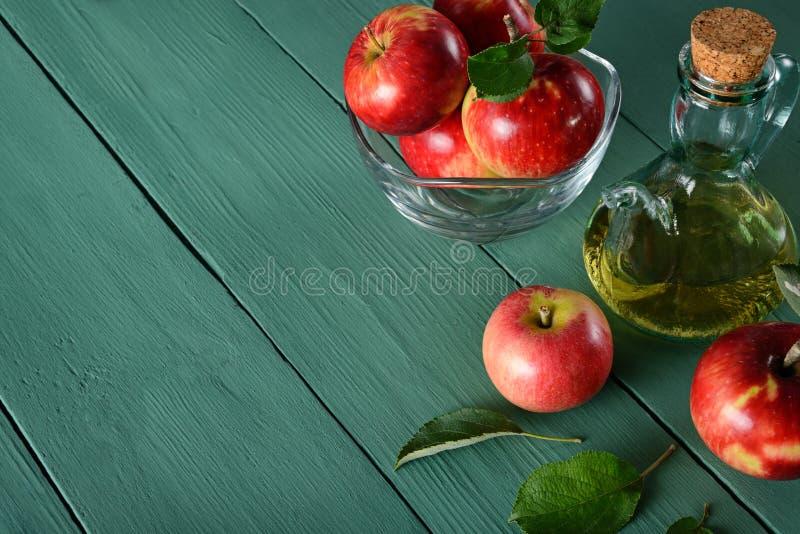 Äppelcidervinäger och mogna röda äpplen på bakgrund av gräsplan w arkivbilder