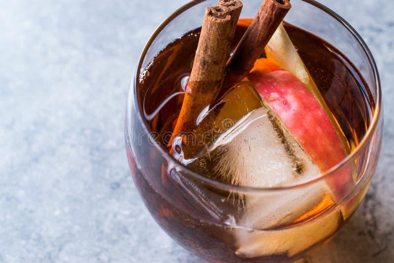 Äppelciderwhiskycoctail med kanelbruna pinnar, is och Apple skivor arkivfoton