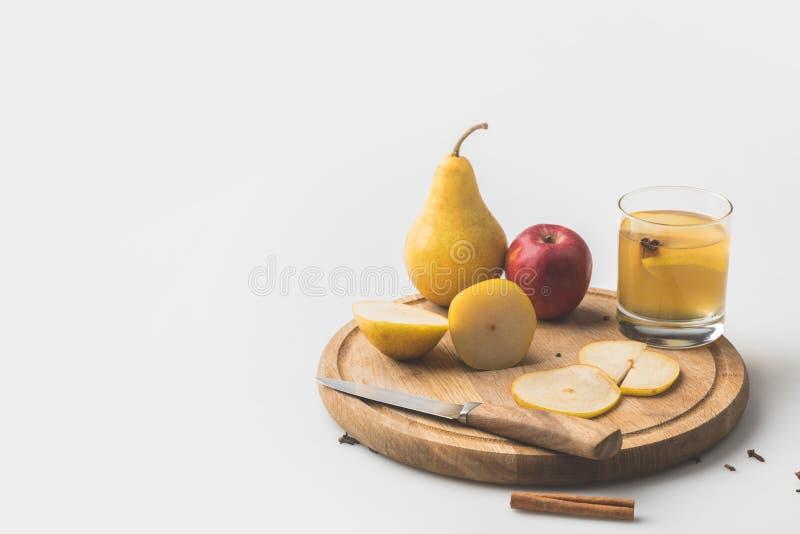 äppeljuice med äpplet och päronet på träbräde royaltyfria bilder