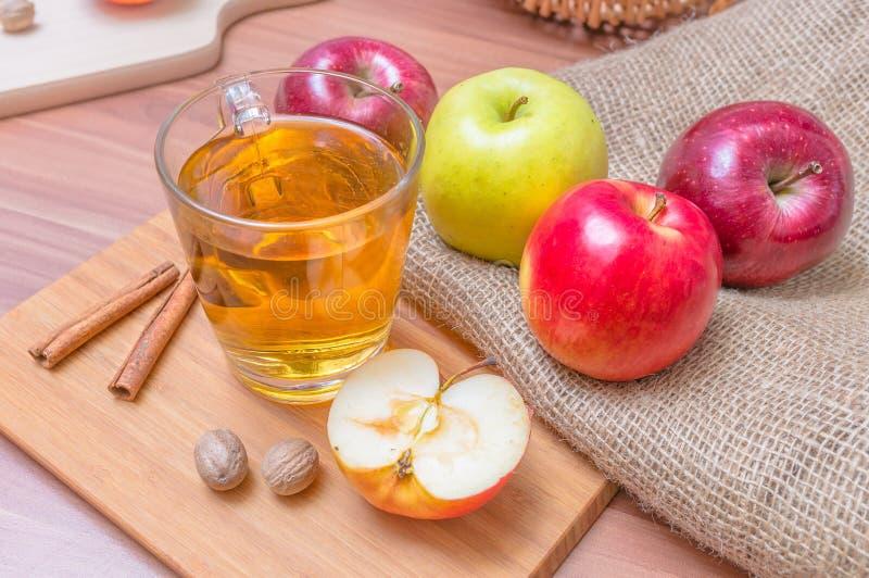Äppeljuice - varma äppledrink och äpplen för alkohol på trätabellen royaltyfri foto