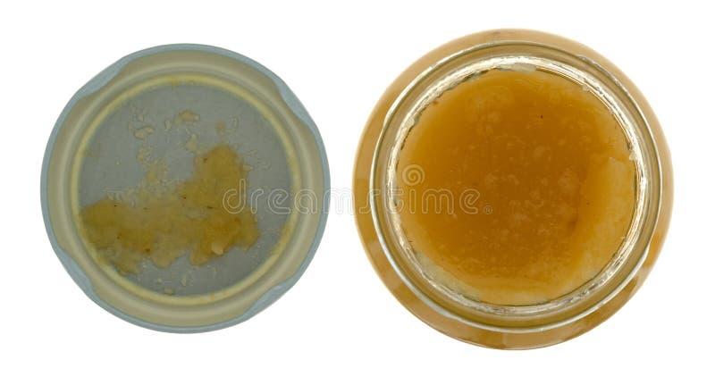 Äppelmos i en öppen exponeringsglaskrus med ett lock till sidan som isoleras på en bästa sikt för vit bakgrund royaltyfri bild