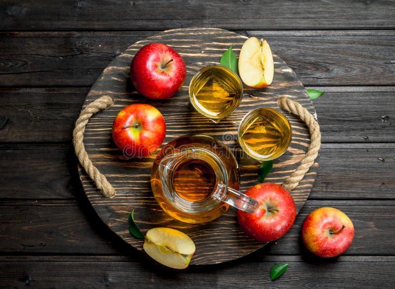 Äppelmust i en exponeringsglaskaraff på en trädressing med nya äpplen arkivfoton