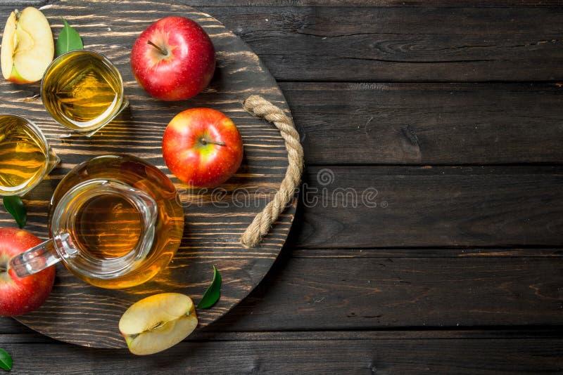 Äppelmust i en exponeringsglaskaraff på en trädressing med nya äpplen arkivbilder