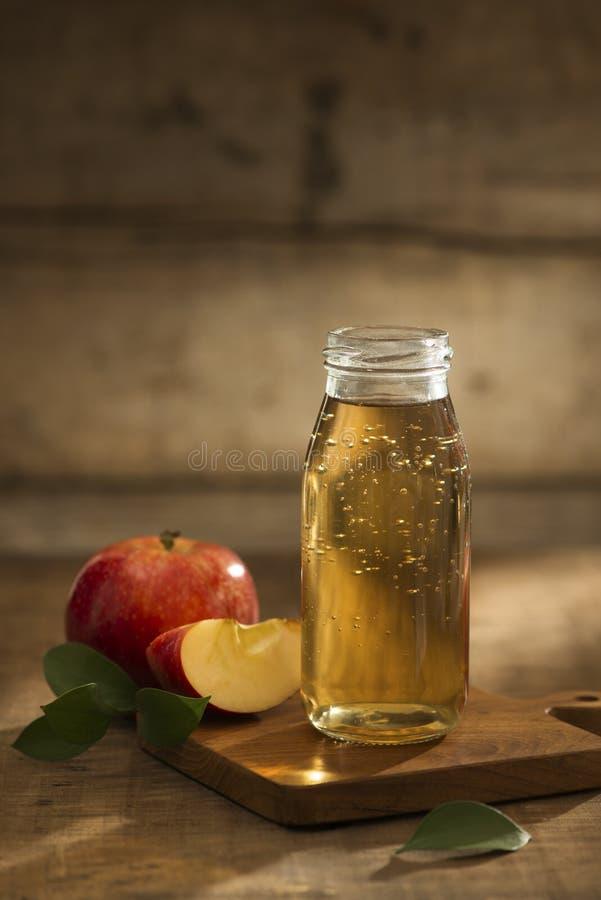 Äppelmust i en flaska och ett exponeringsglas med det skivade röda äpplet i träbakgrund royaltyfria bilder