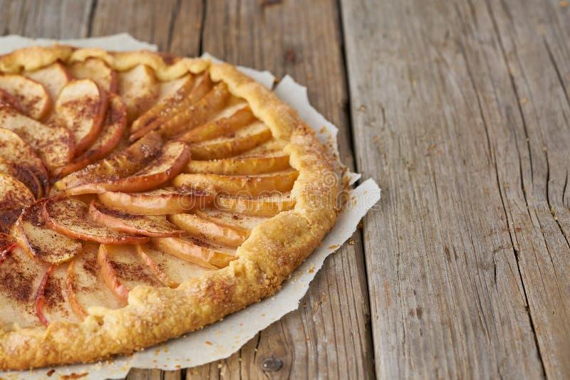 Äppelpaj galette med frukter, söta bakelser på den gamla trälantliga tabellen, sidosikt, kopieringsutrymme royaltyfria foton