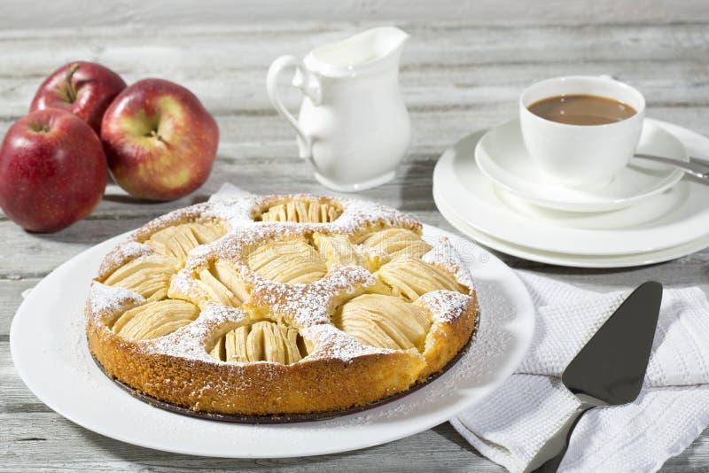 Äppelpaj, kaffekopp och platta, äpplen på trä arkivfoton