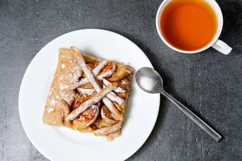 Äppelpaj med en kopp te på mörk stenbakgrund Stycke för äppelpajäpplekopp te av kakan läcker efterrätt arkivfoto